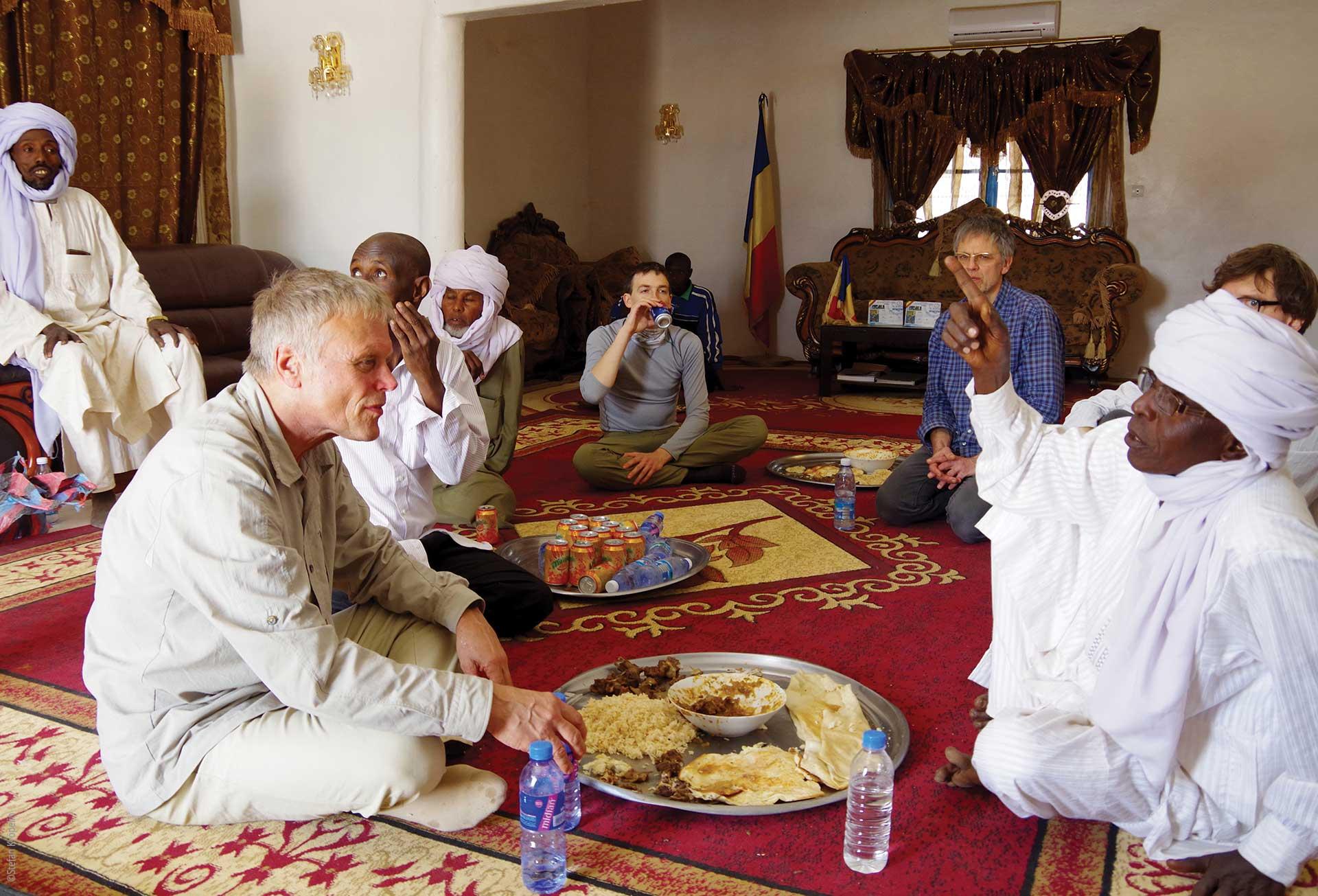 Forschungen und Expeditionen im Norden des Tschad, Zusammenarbeit mit der Bevölkerung, Expeditionsteilnehmer und Bewohner beim gemeinsamen Essen, Explore Chad