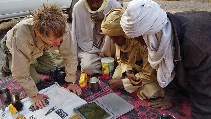 Expedition nach Ounianga, Expeditionsteilnehmer studieren Karten der Region am Laptop, Explore Chad