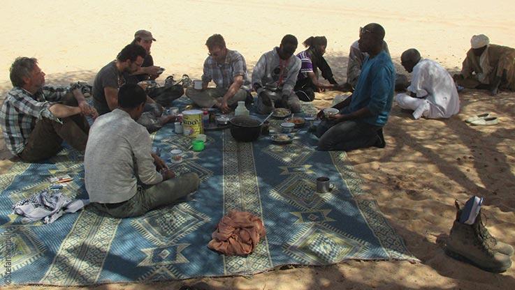 Expedition nach Ounianga, Expeditionsteam beim Essen auf der Matte, Explore Chad