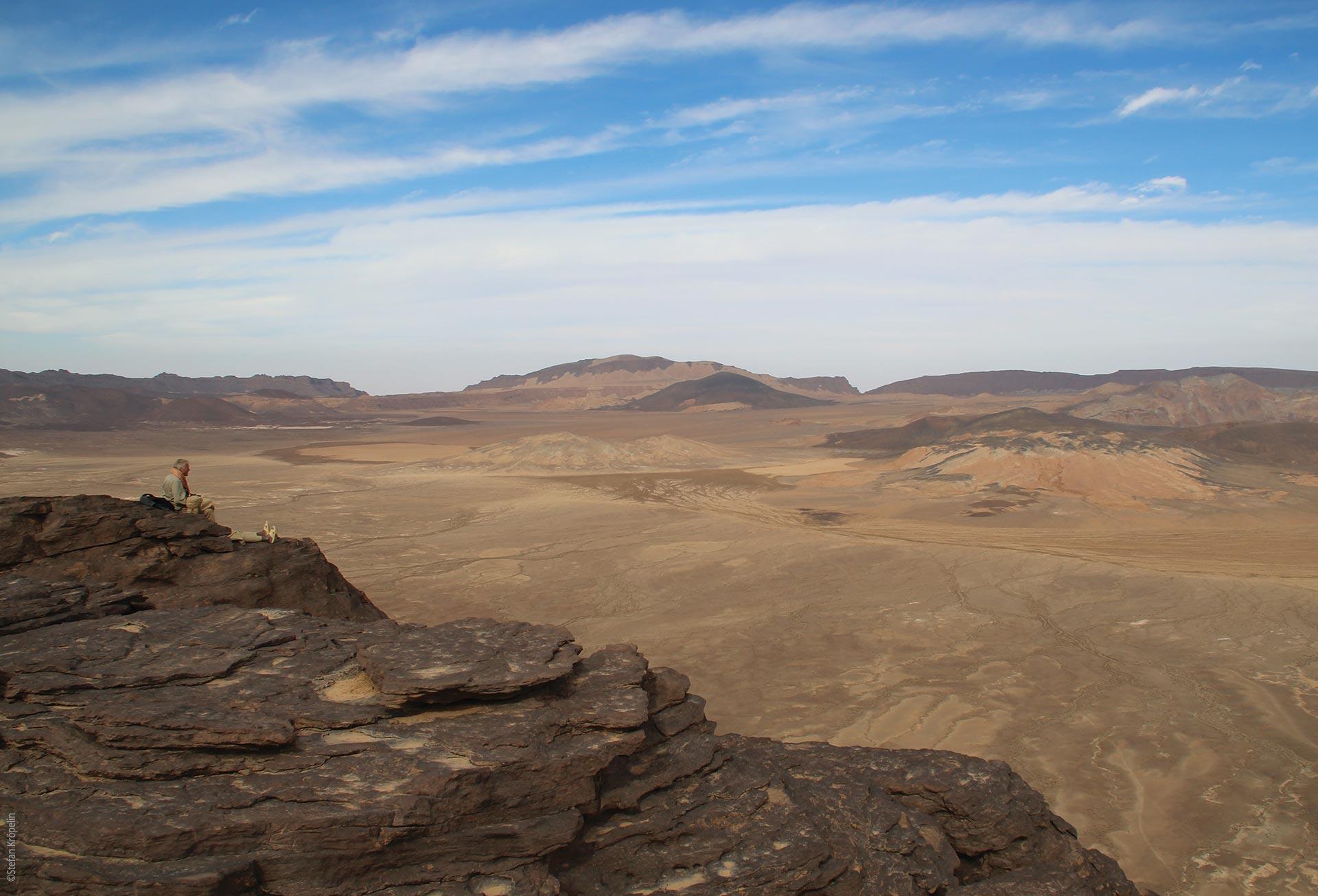 Das Tibesti Gebirge, Emi Koussi, Caldera, Stefan Kröpelin am Felsrand sitzend, Explore Chad