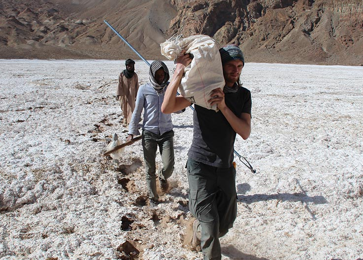 The Tibesti Mountains, Trou au Natron, members of the expedition carrying samples and walking on a crusty layer of salt, Explore Chad